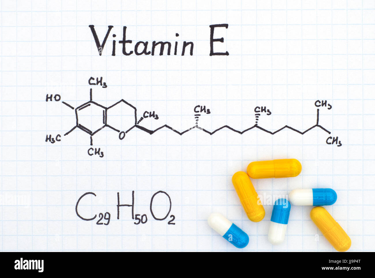 Chemical formula of Vitamin E with some pills. - Stock Image