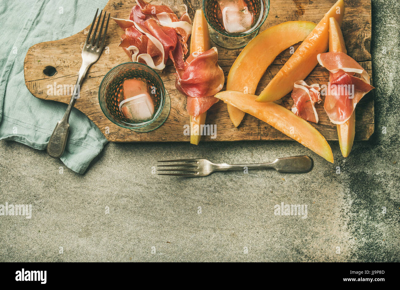 Summer wine party set with rose wine, prosciutto and melon - Stock Image
