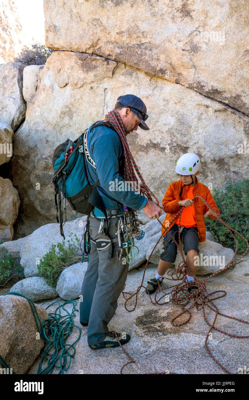 A father teaches his 9 year old son to coil a rope after climbing a route in Joshua Tree National Park, California. - Stock Image