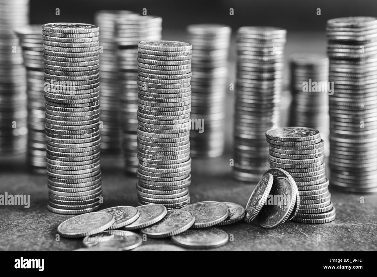 Black and white picture of coins stacks, shallow depth of field. - Stock Image