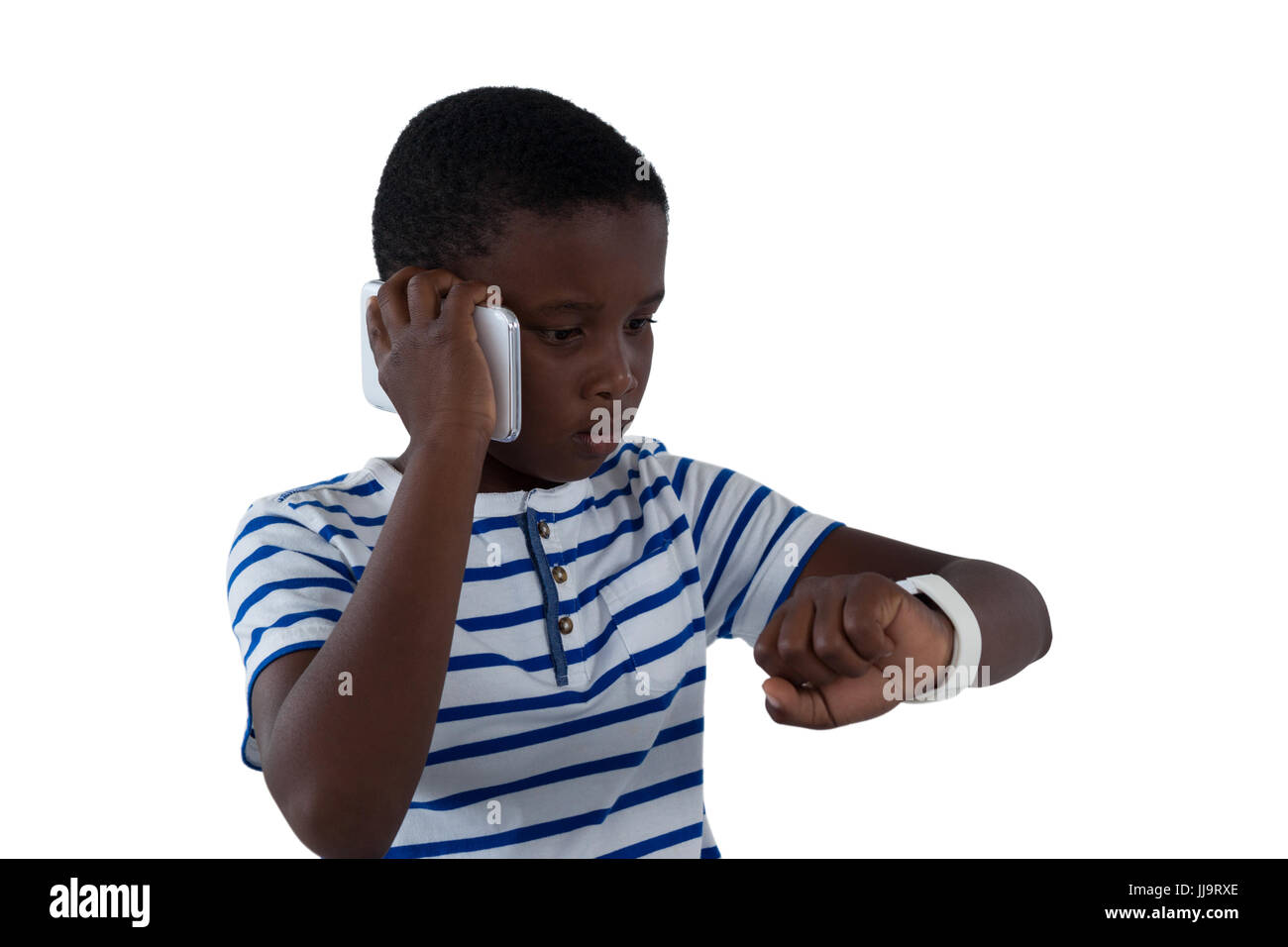 Boy looking at his smart watch while talking on mobile phone against white background - Stock Image