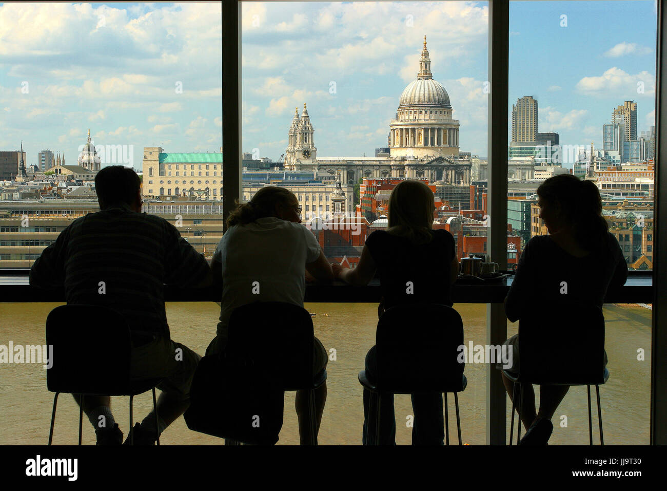 Rear view shot of tourists looking through window at view of St Paul's Cathedral, London, England, UK - Stock Image