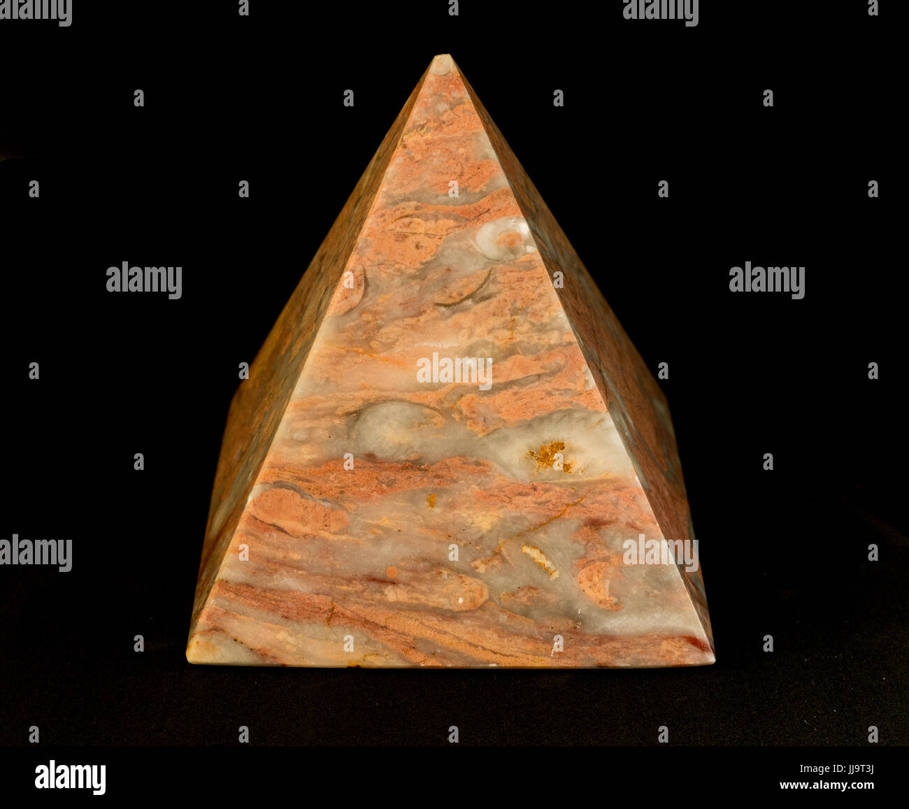 Still life of peach coloured marble pyramid against a black background - Stock Image