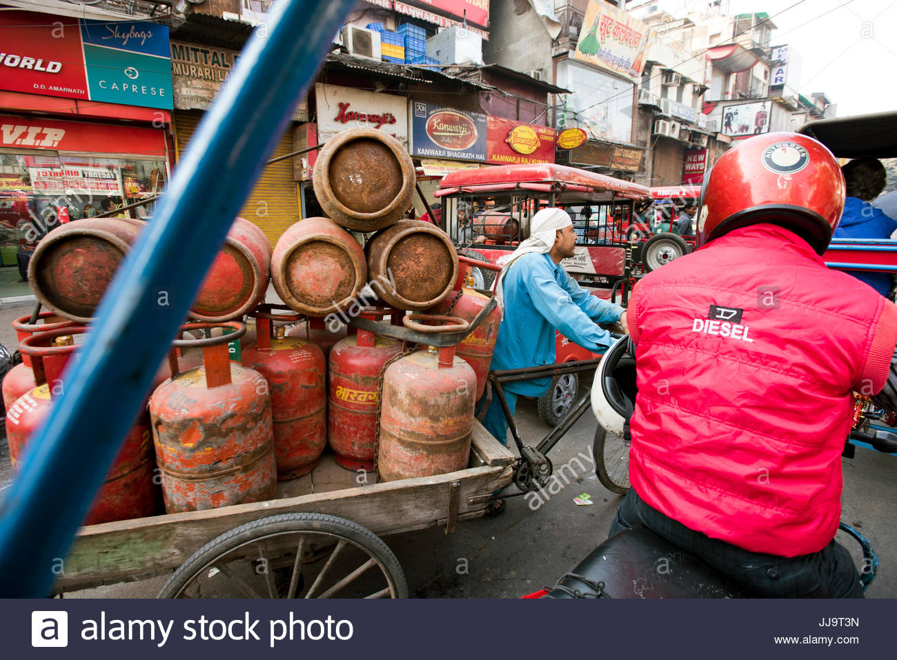 An Indian man carries takes of propane on his bicycle rickshaw in New Delhi, India. - Stock Image