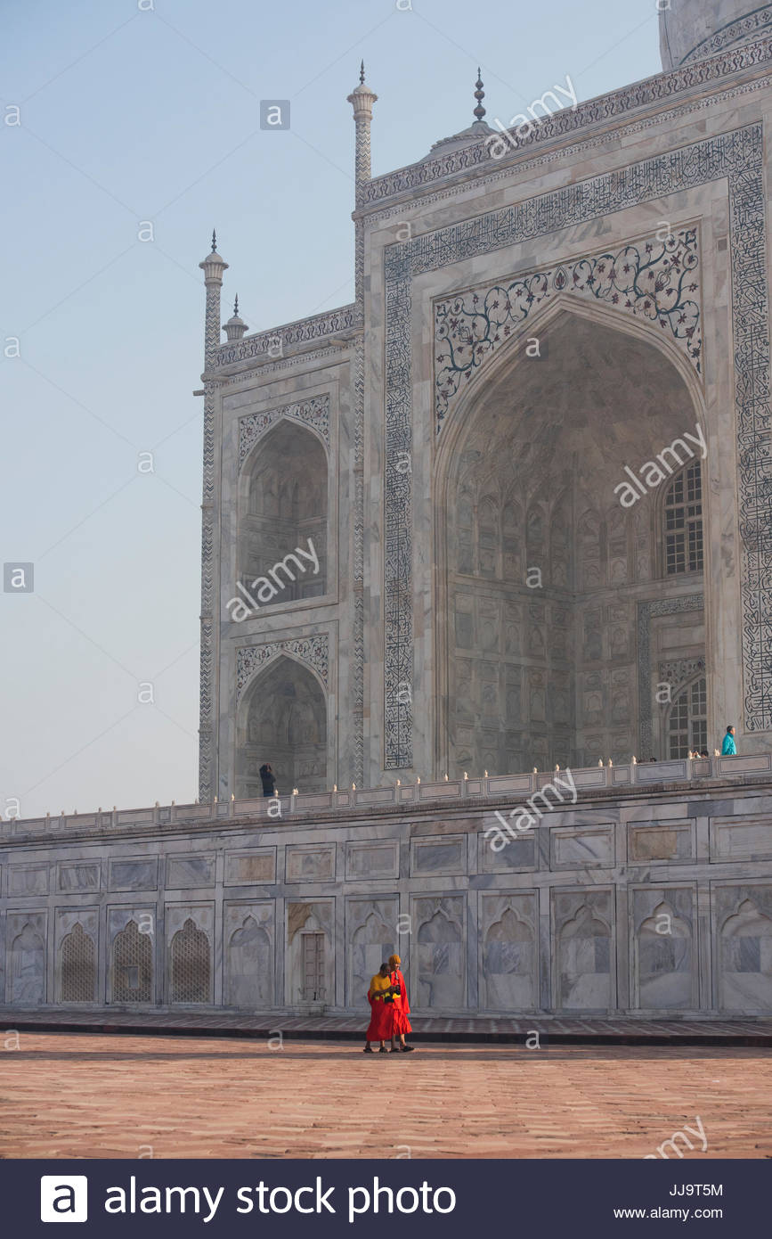 Two monks walks in front of the Taj Mahal in Agra, India. - Stock Image