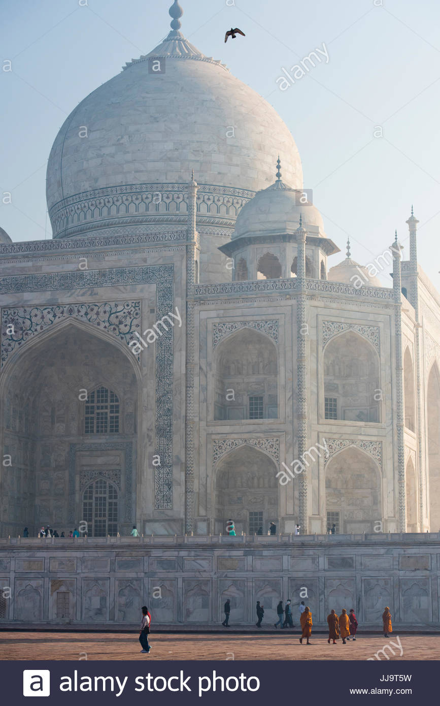 Walking tourists are dwarfed by the size of the Taj Mahal in Agra, India. - Stock Image