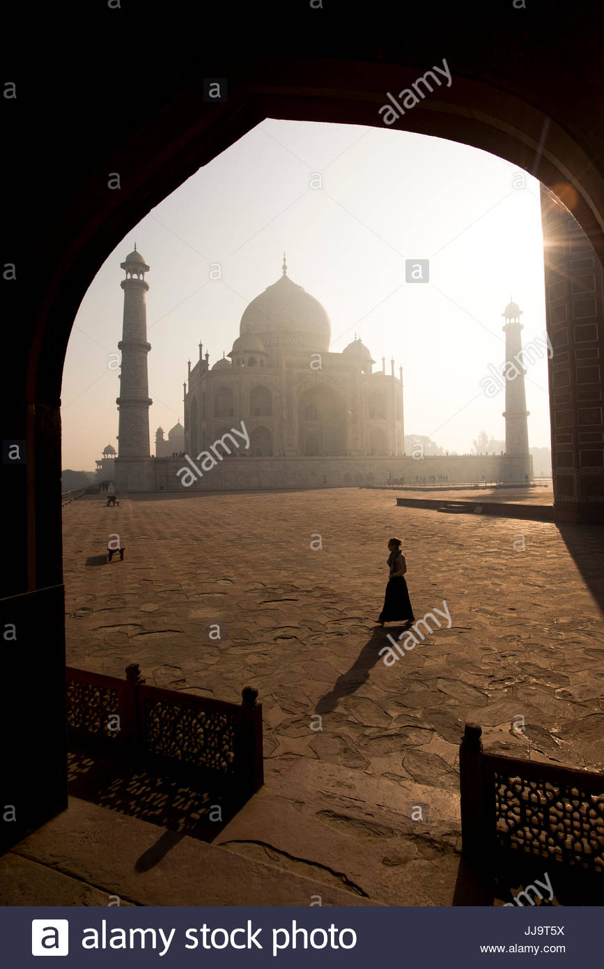 A girl walks in front of the Taj Mahal on a sunny morning in Agra, India. - Stock Image