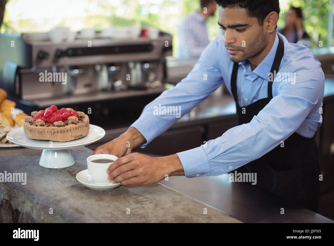 Waiter serving coffee at counter in commercial kitchen - Stock Image