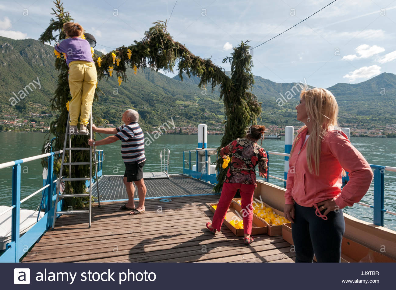 Decorating village with pine branches and paper flowers festoons, Festa di Santa Croce, Carzano, Lake Iseo, Italy - Stock Image