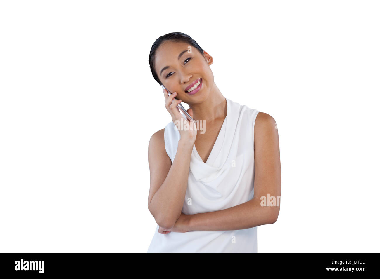 Happy businesswoman with head cocked talking on mobile phone while standing against white background - Stock Image