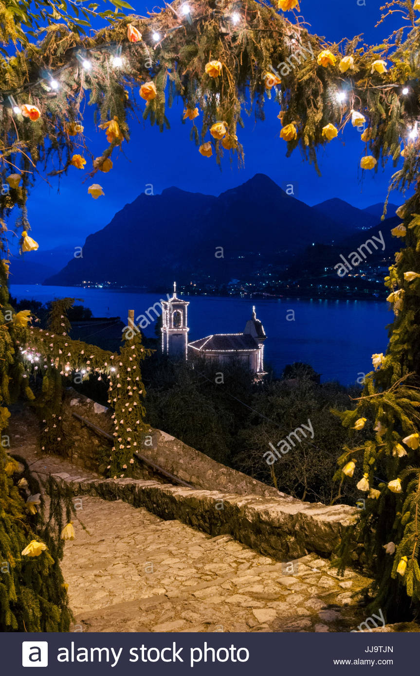 Village decorated with pine branches, paper flowers festoons and luminarias, Festa di Santa Croce, Carzano, Lake - Stock Image