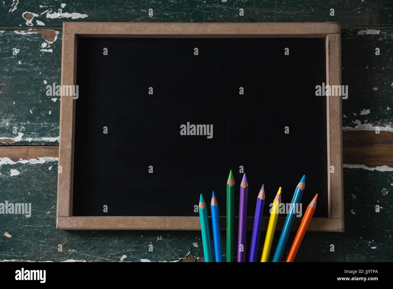 Close-up of blank chalkboard and various colored pencil - Stock Image