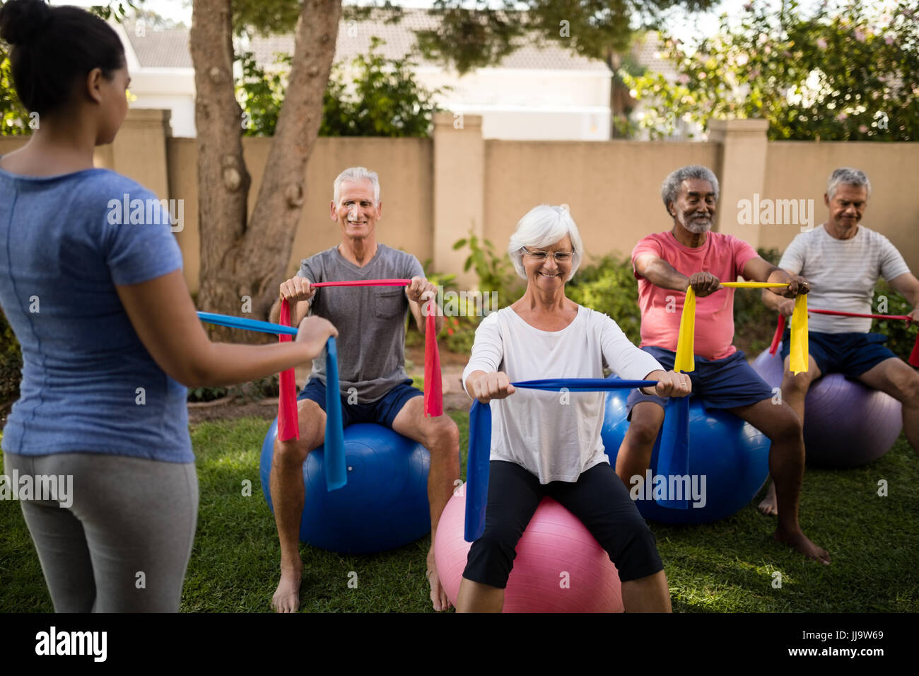 Trainer guiding senior people while exercising with multi colored ribbons and balls at park - Stock Image