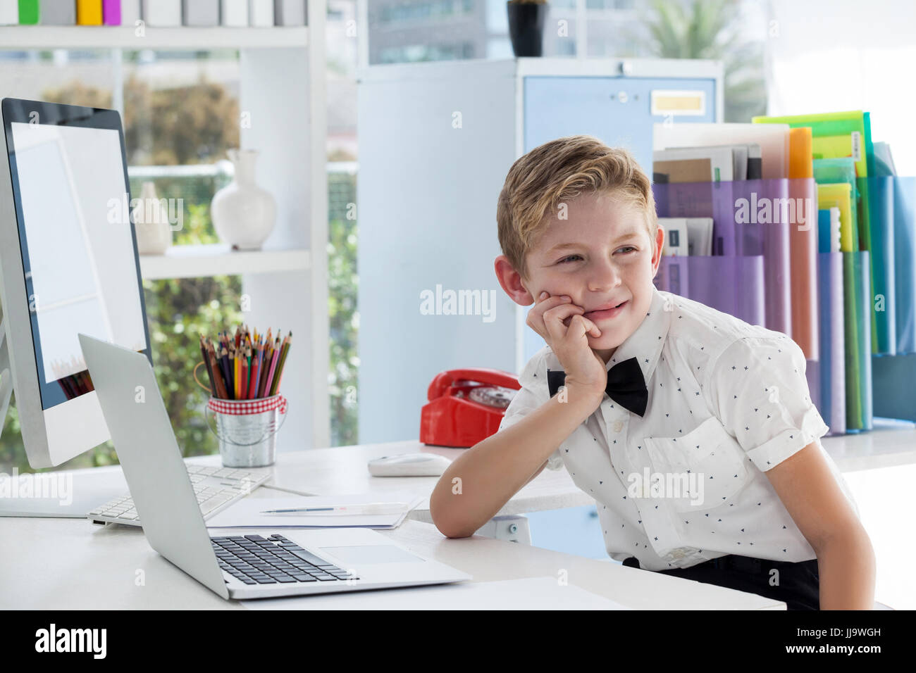 Thoughtful businessman with hand on chin looking away while sitting by laptop at desk in office - Stock Image