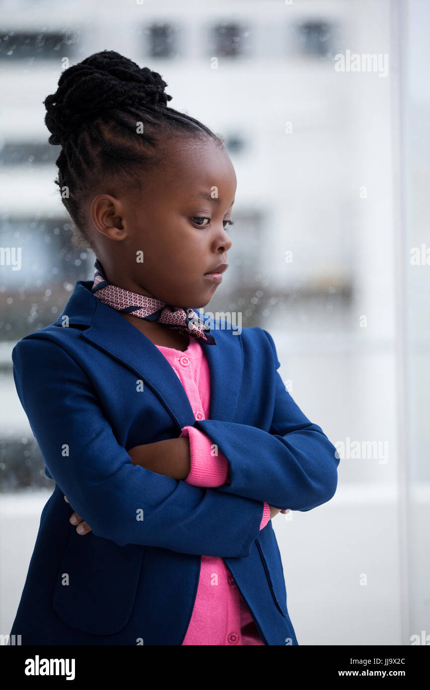 Thoughtful businesswoman with arms crossed standing by window at office - Stock Image