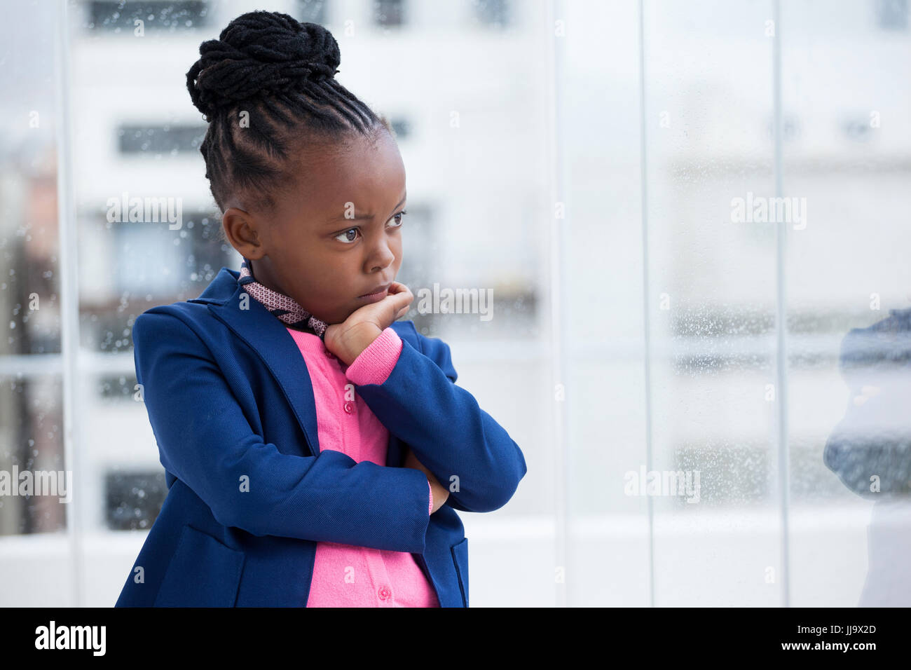 Thoughtful businesswoman with hand on chin standing by glass window at office - Stock Image