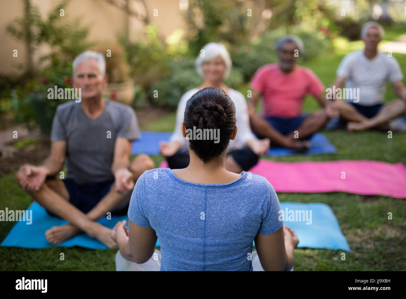 Rear view of trainer guiding senior people in meditating exercise at park - Stock Image