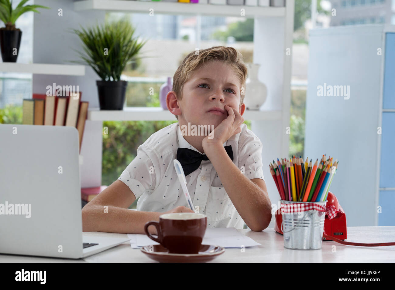 Thoughtful businessman with hand on chin sitting at desk in office - Stock Image