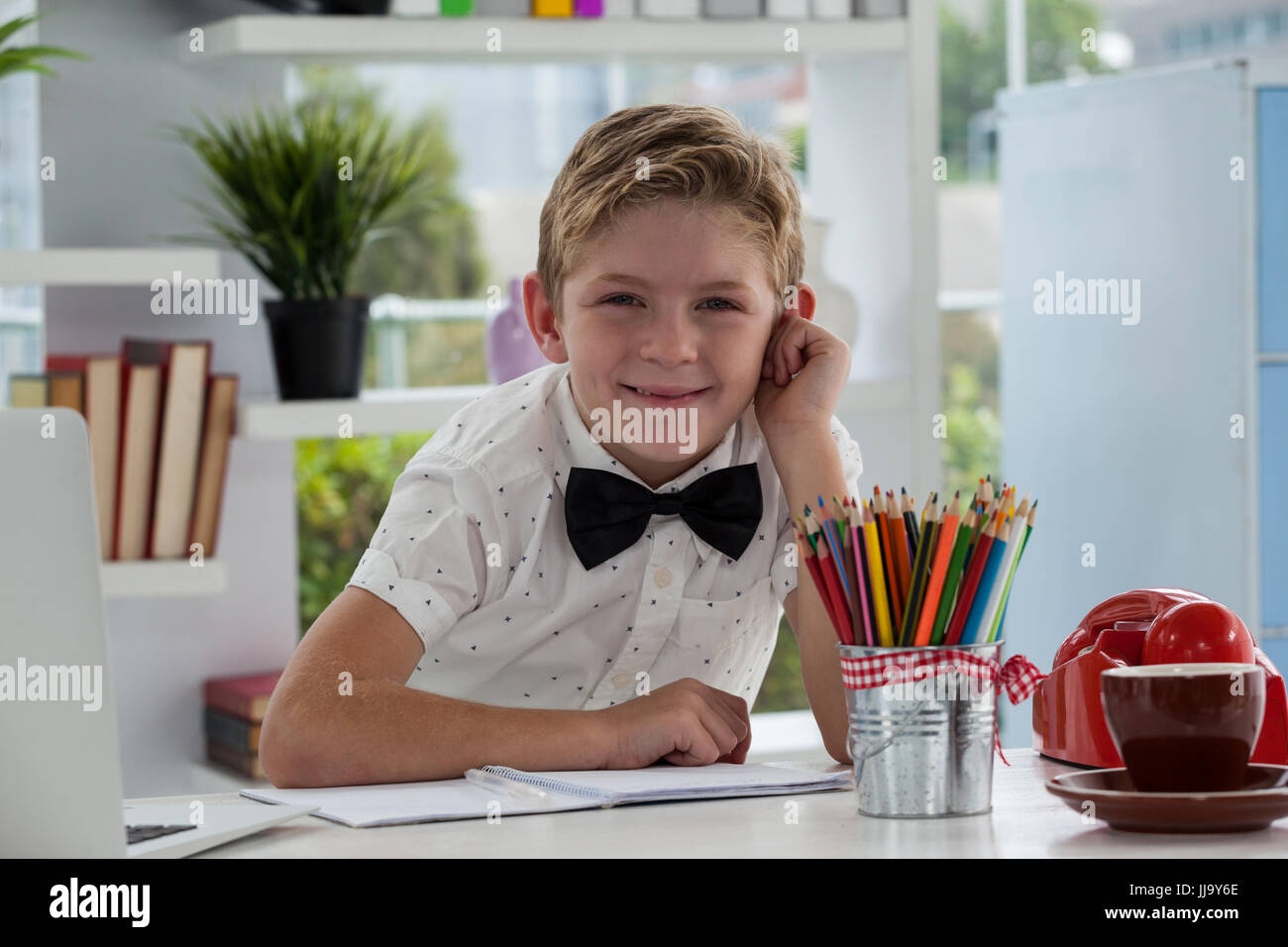 Portrait of smiling businessman with documents at desk in office - Stock Image