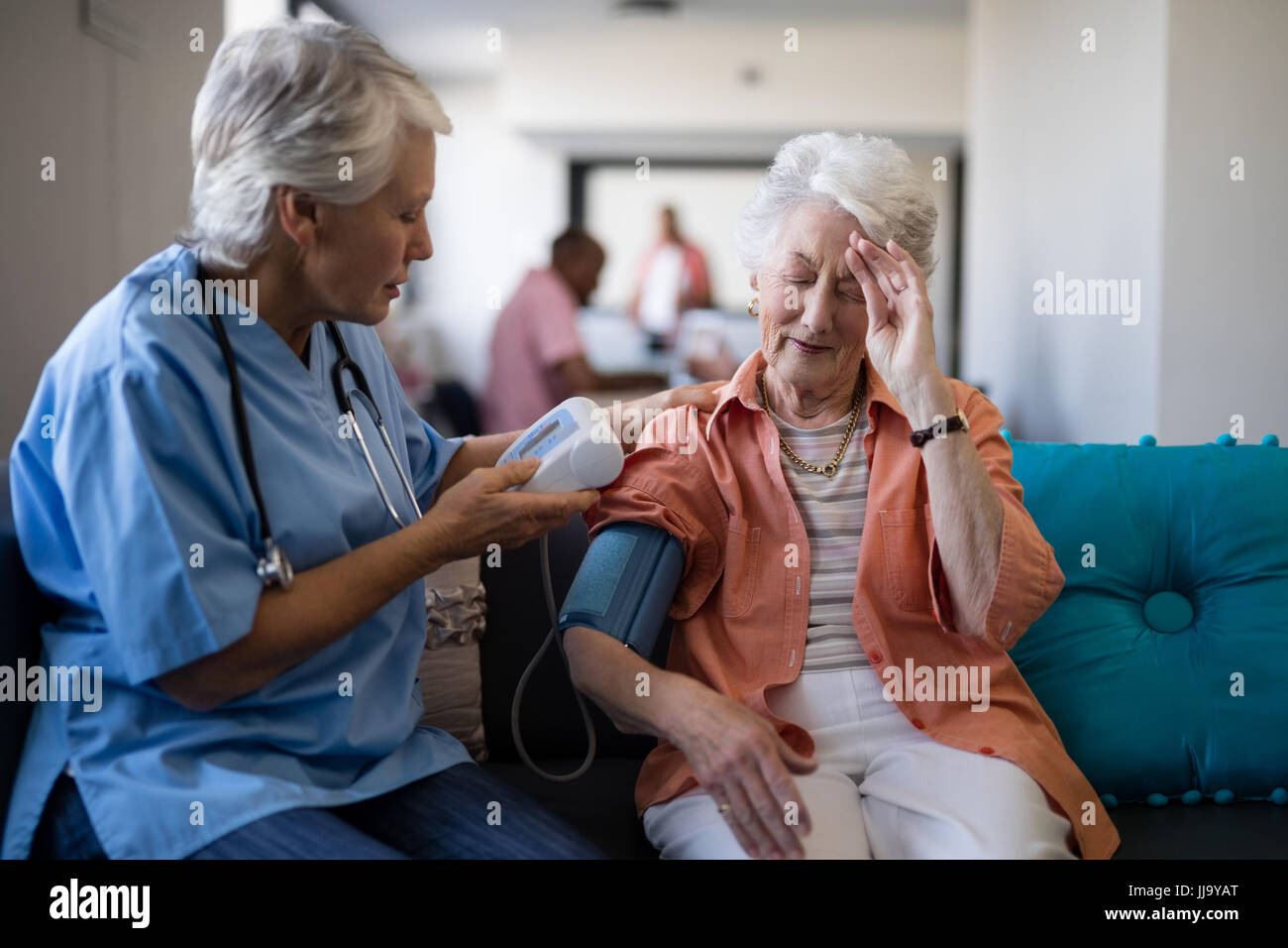 Senior woman complaining about headache to doctor during blood pressure check up at nursing home - Stock Image