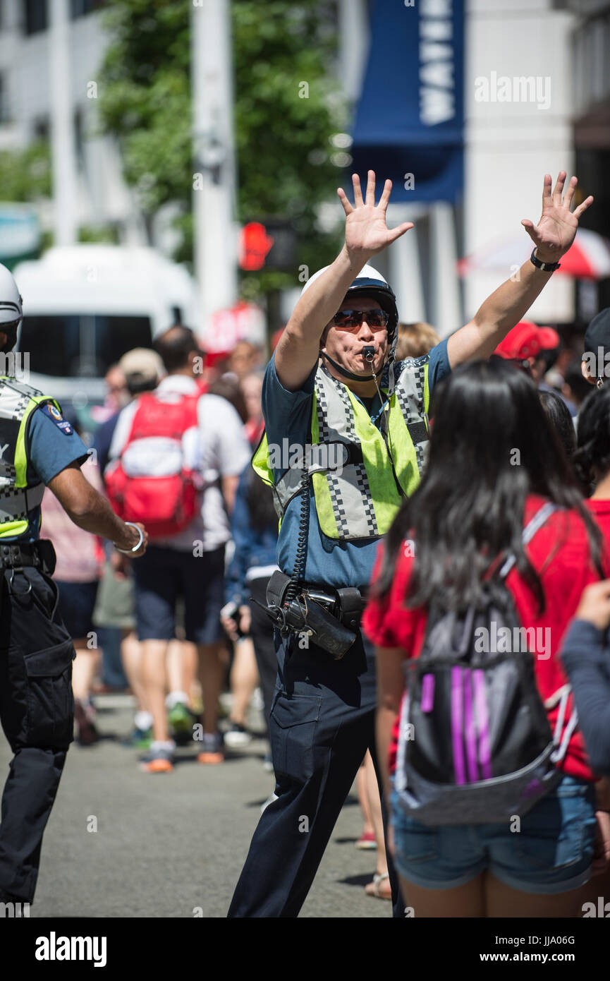 Vancouver city policeman signalling with hands raised for pedestrians to stop. - Stock Image