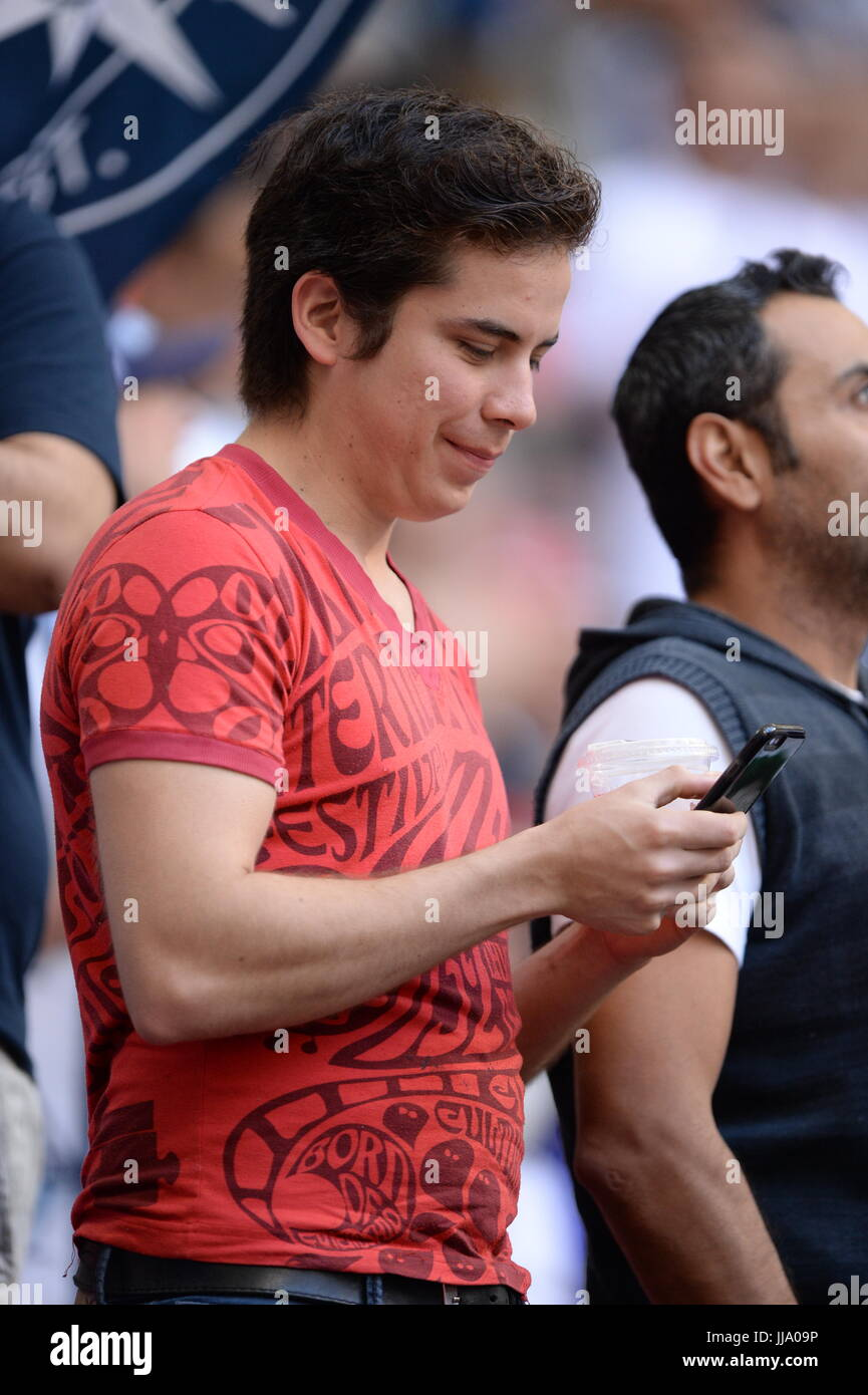Sport Fan checking their phone. - Stock Image