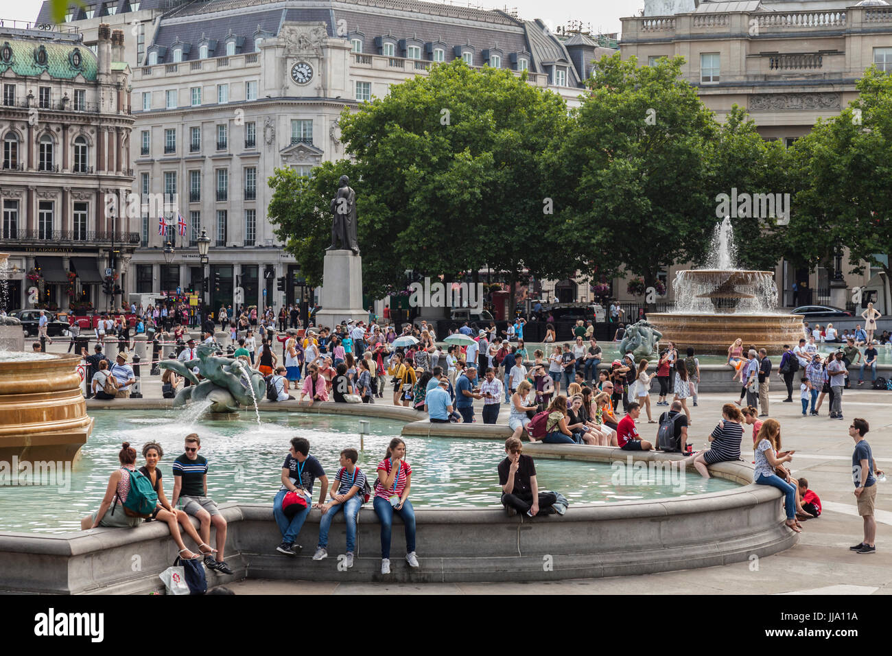 Crowds of people, mainly tourists, around the fountains in Trafalgar square in central London, England, UK - Stock Image