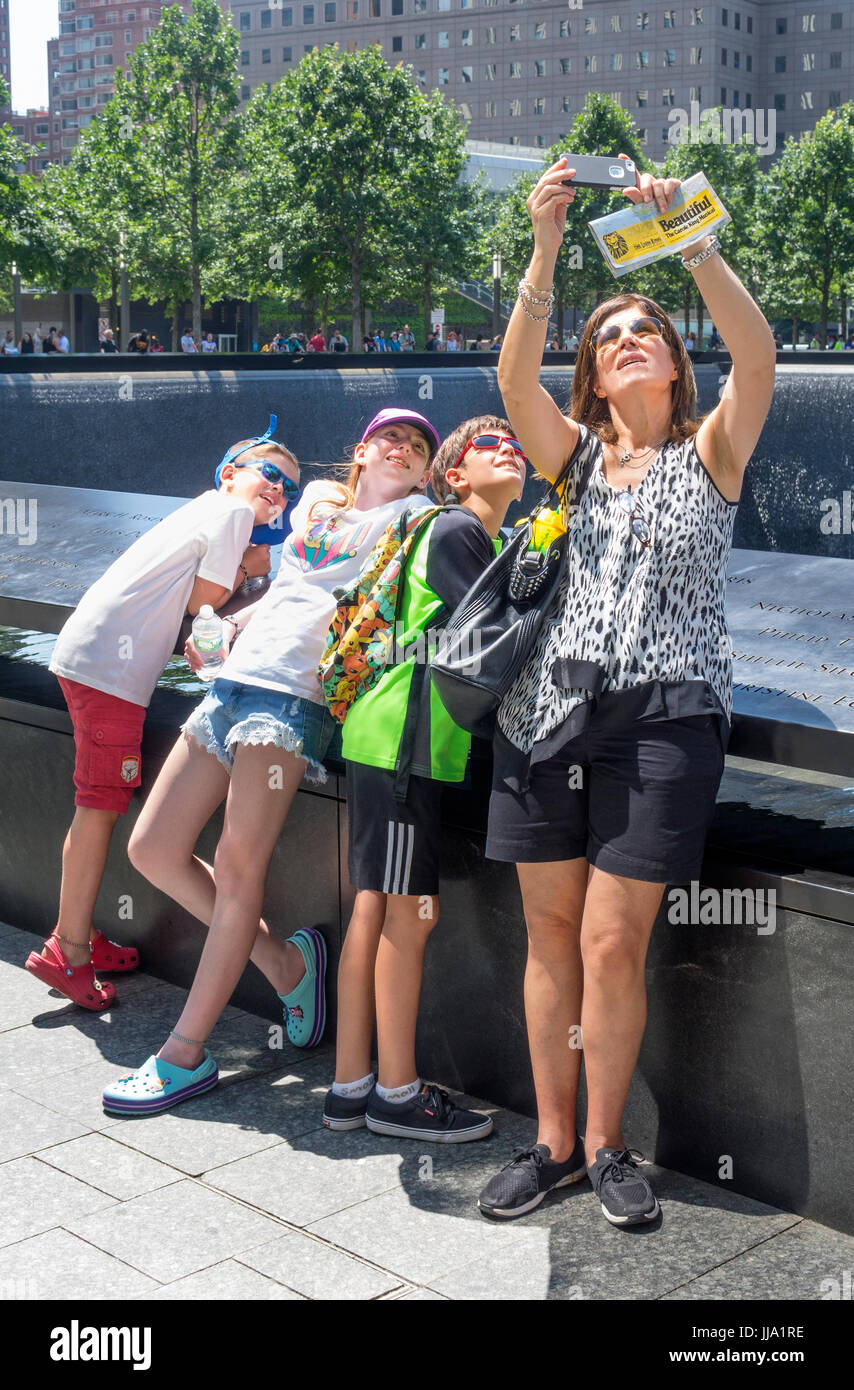 Mother taking a family selfie with her three children at the South Pool of World Trade Center in New York City - Stock Image