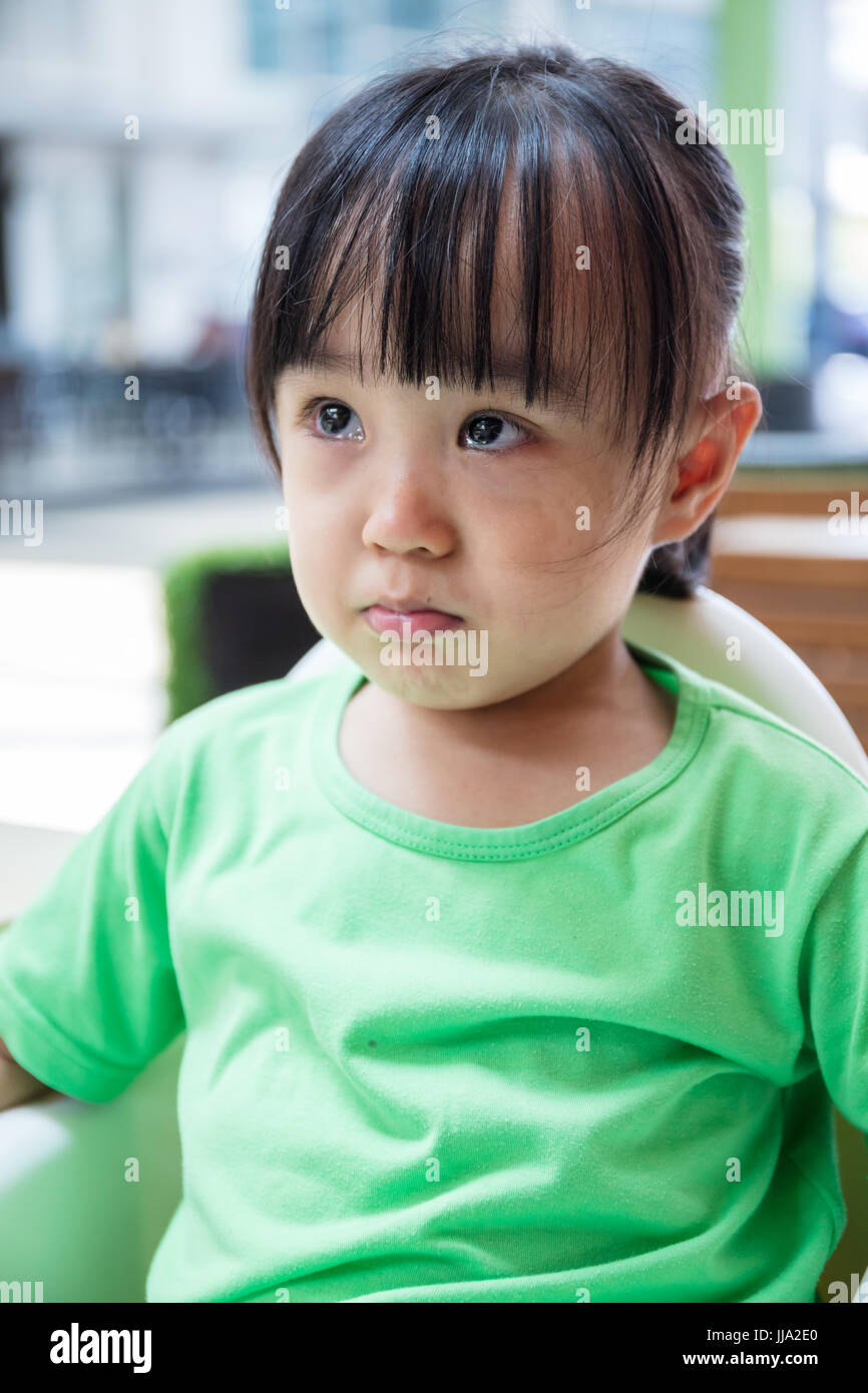 Asian Chinese little girl crying at outdoor restaurant - Stock Image