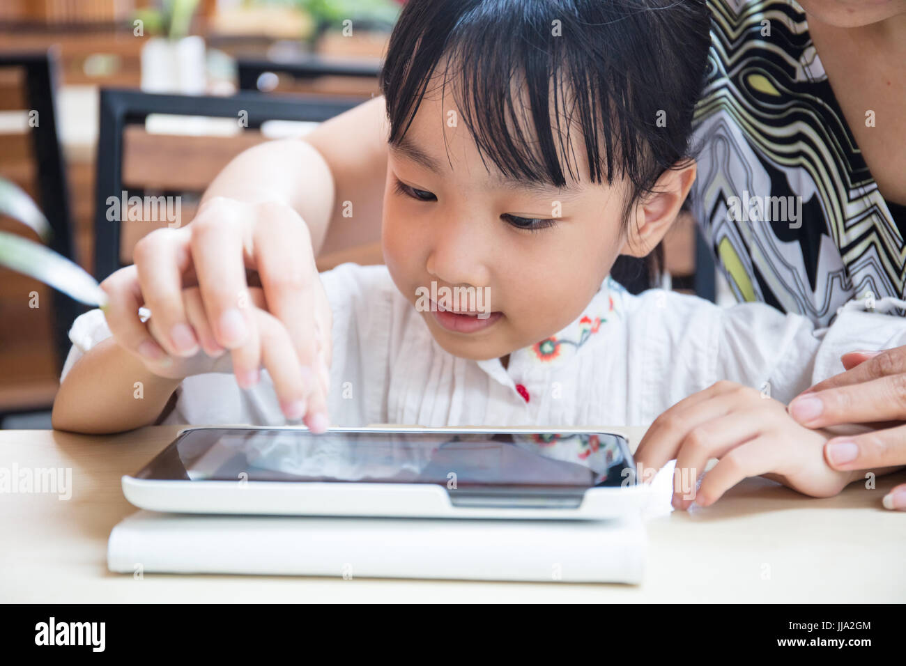 Asian Chinese little girl playing tablet computer with her mother at outdoor cafe - Stock Image