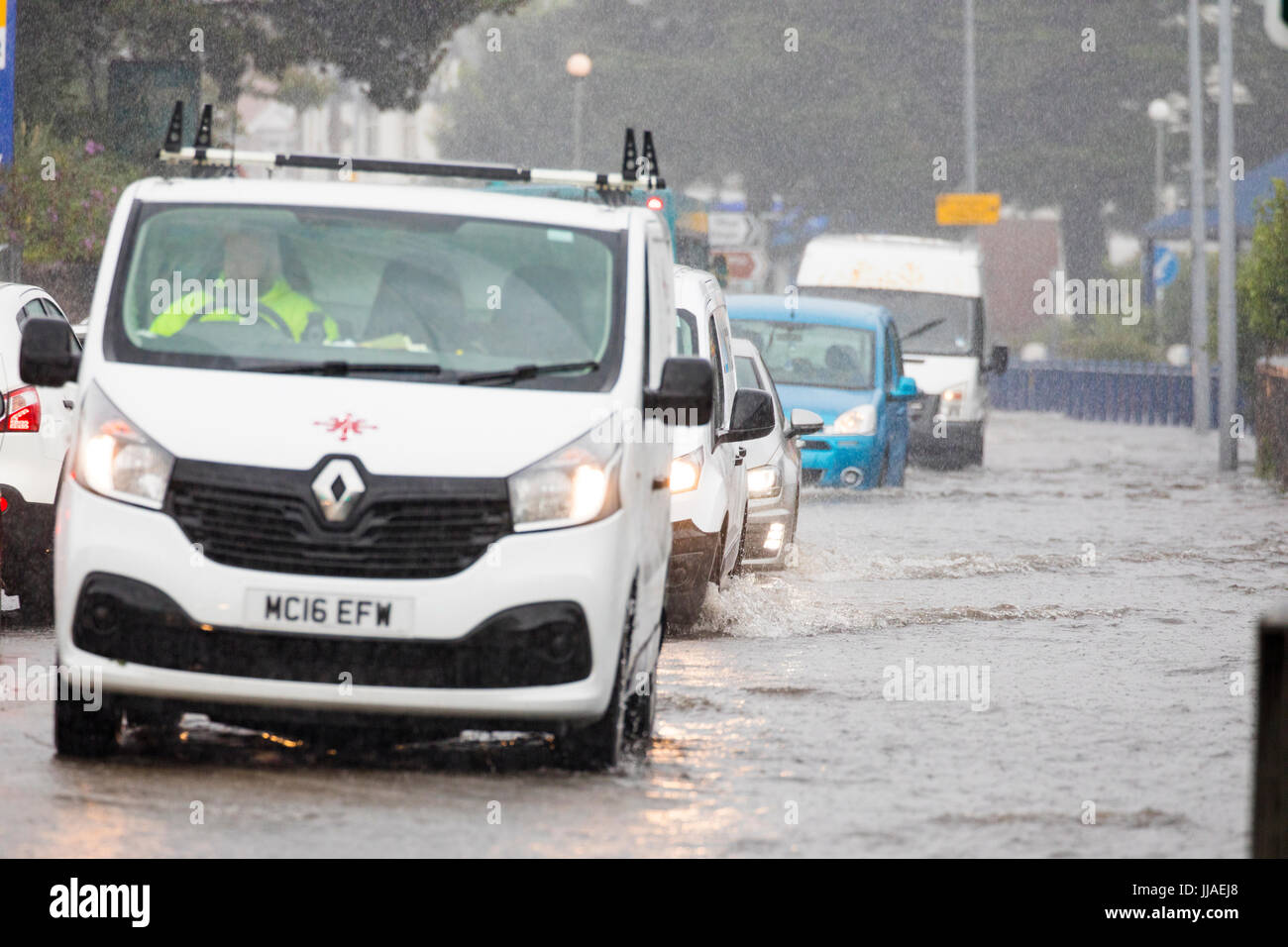 Drivers caught out by flash flooding during torrential rain storms driving through the flooded roads in Rhyl, North - Stock Image