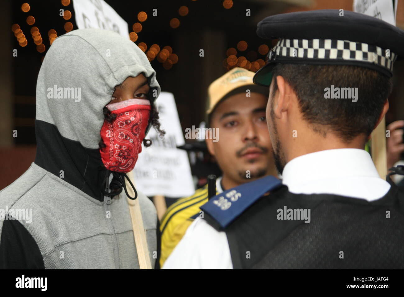 London, UK. 19th July 2017. A policeman faces a couple of young protesters.  Protests take place outside the Kensington and Chelsea Council building as the council meets to  discuss the Grenfell disaster a month after it happened. Roland Ravenhill/Alamy Live News. Credit: Roland Ravenhill/Alamy Live News Stock Photo