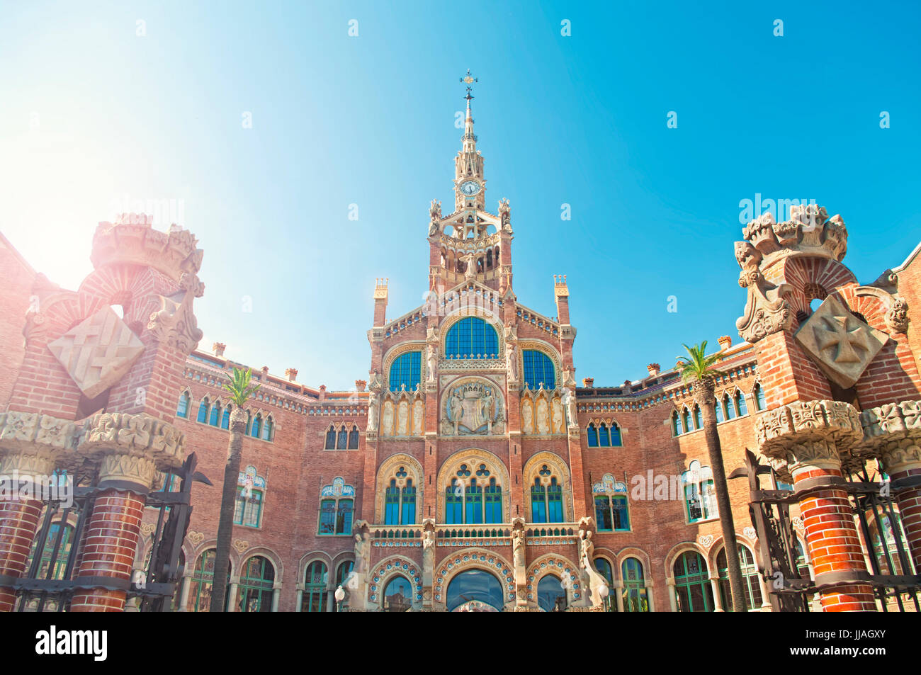 cross-processed image of Hospital of the Holy Cross and Saint Paul against clear blue sky on sunny summer day, Barcelona, - Stock Image