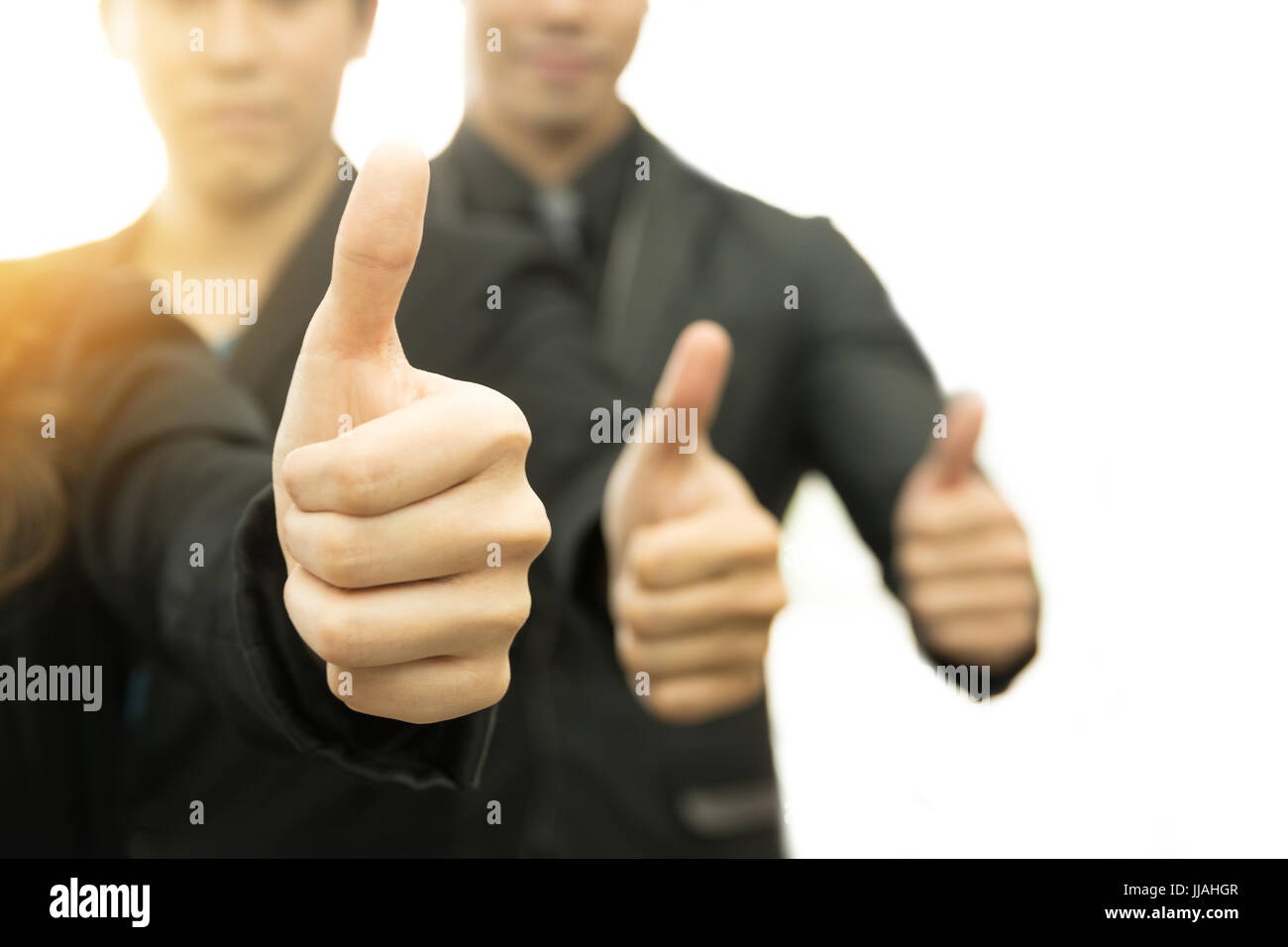 Business success concept Selective focus on thumbs up of business man on white background. Warm tone with flare - Stock Image