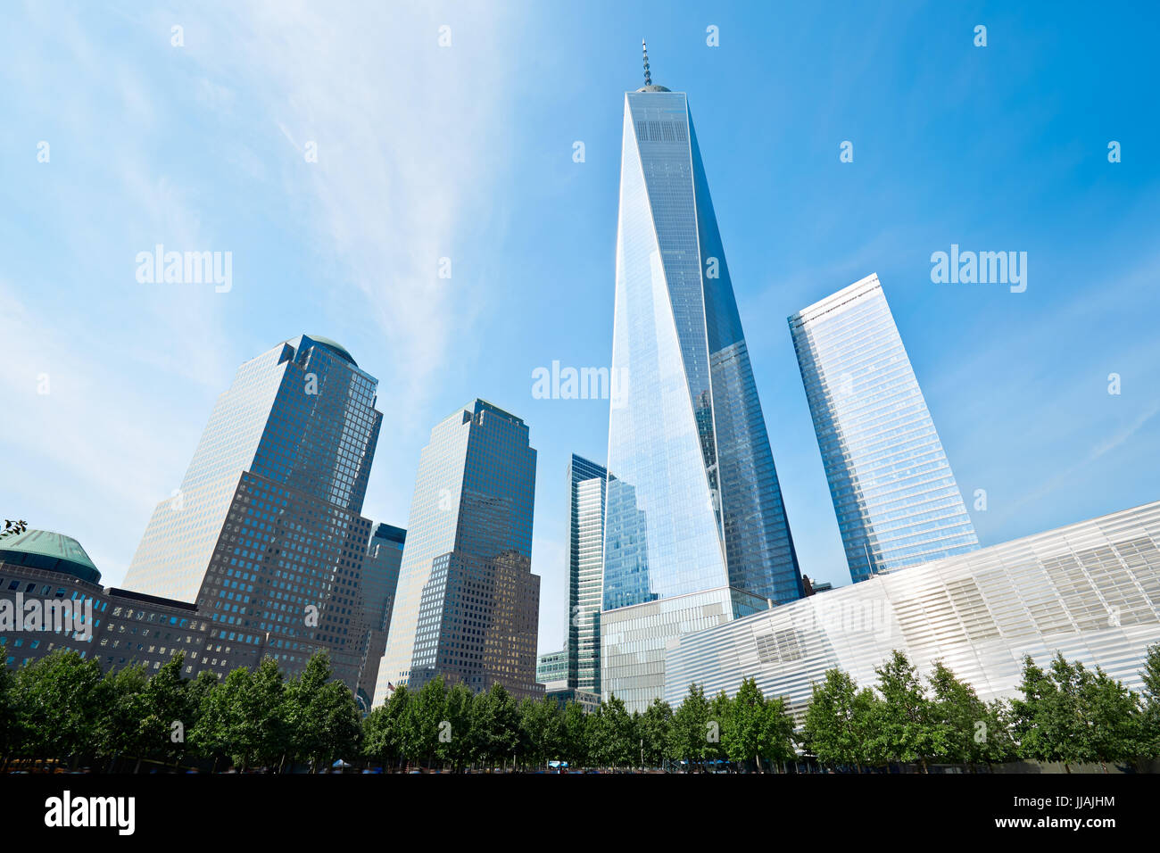 One World Trade Center skyscraper surrounded by glass buildings and green trees, blue sky in New York - Stock Image