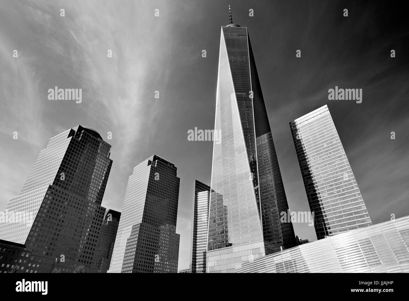 One World Trade Center skyscraper surrounded by glass buildings, black and white in a sunny day in New York - Stock Image