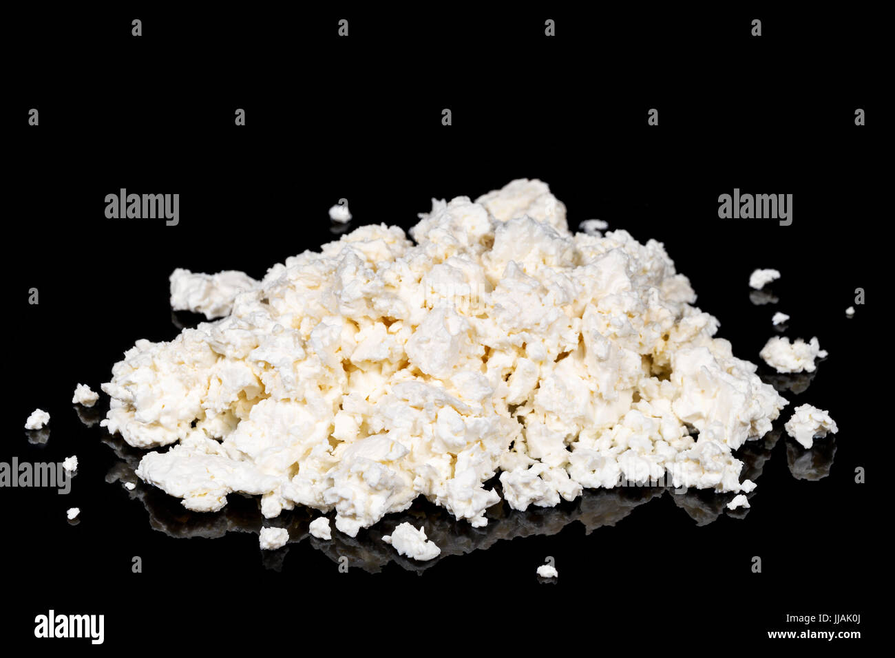 Pile of cottage cheese on black - Stock Image