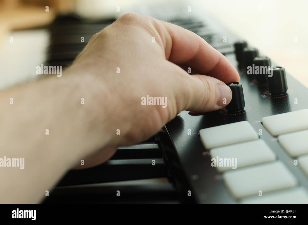 Man's hand sets the synthesizer. Side view - Stock Image