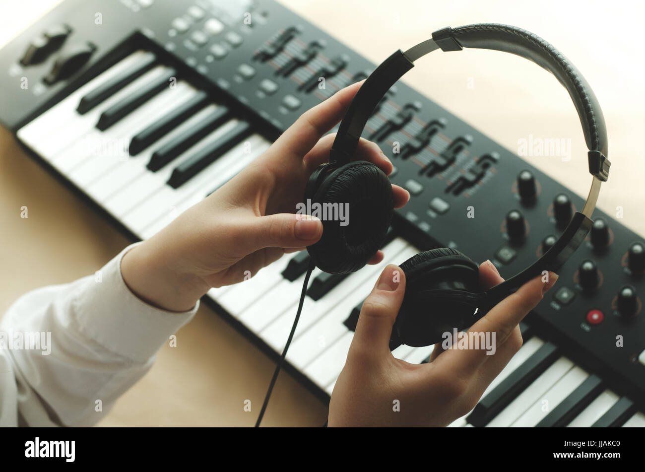 A woman in a white shirt is holding headphones in front of a synthesizer. There are two hands in the frame - Stock Image