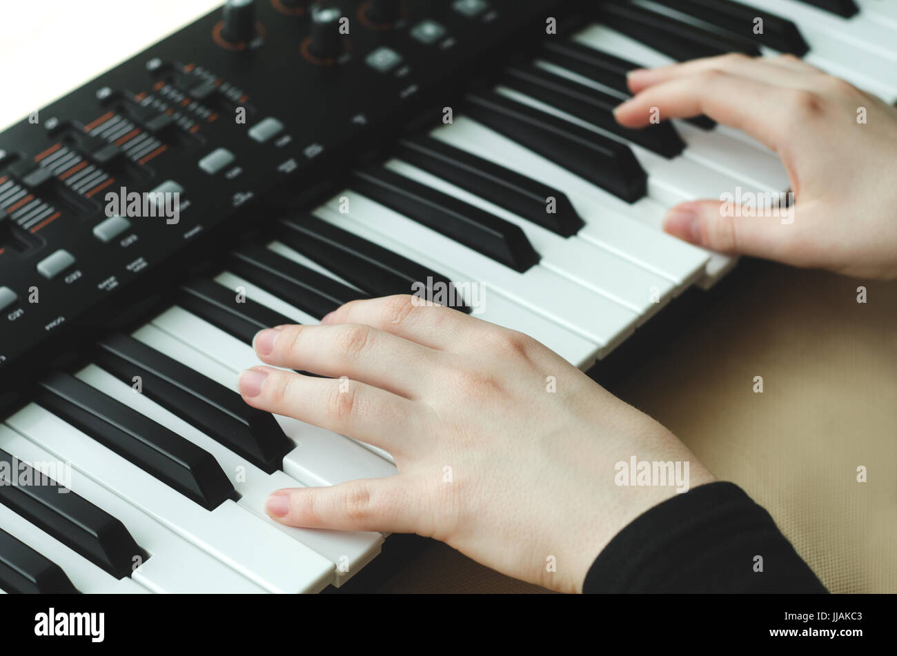 A woman in a black jacket plays a synthesizer. There are two hands in the frame. - Stock Image