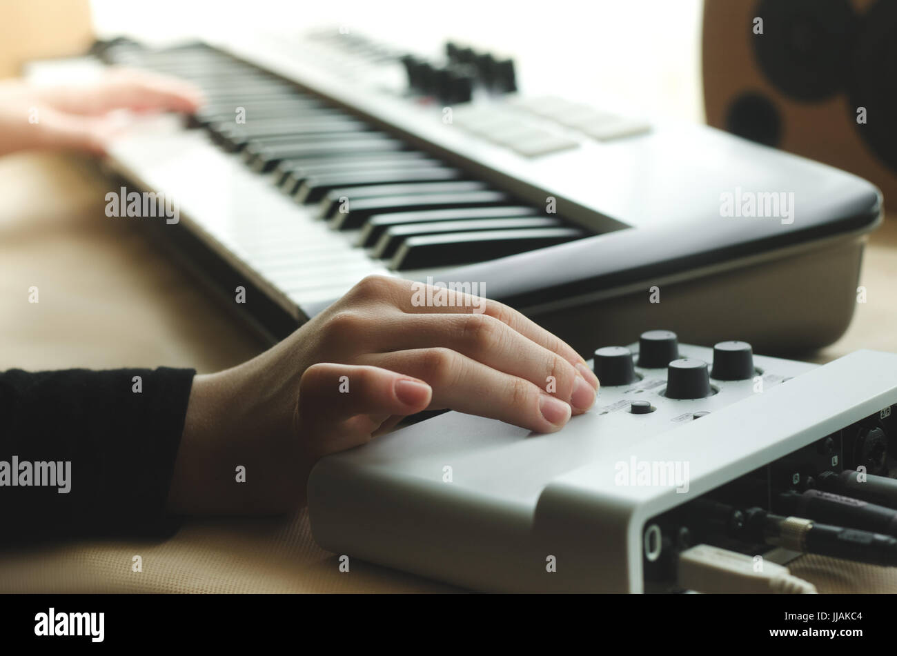 A woman in a black jacket adjusts the synthesizer on the music console, while the other hand plays the synthesizer - Stock Image