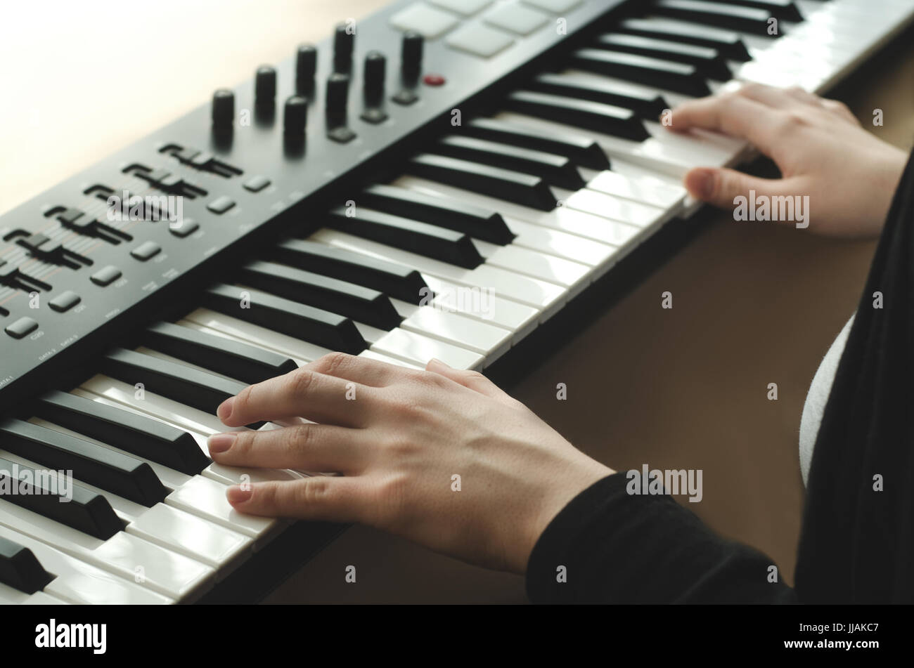 A woman in a black jacket plays a synthesizer against the window. The body in the frame. Side view - Stock Image