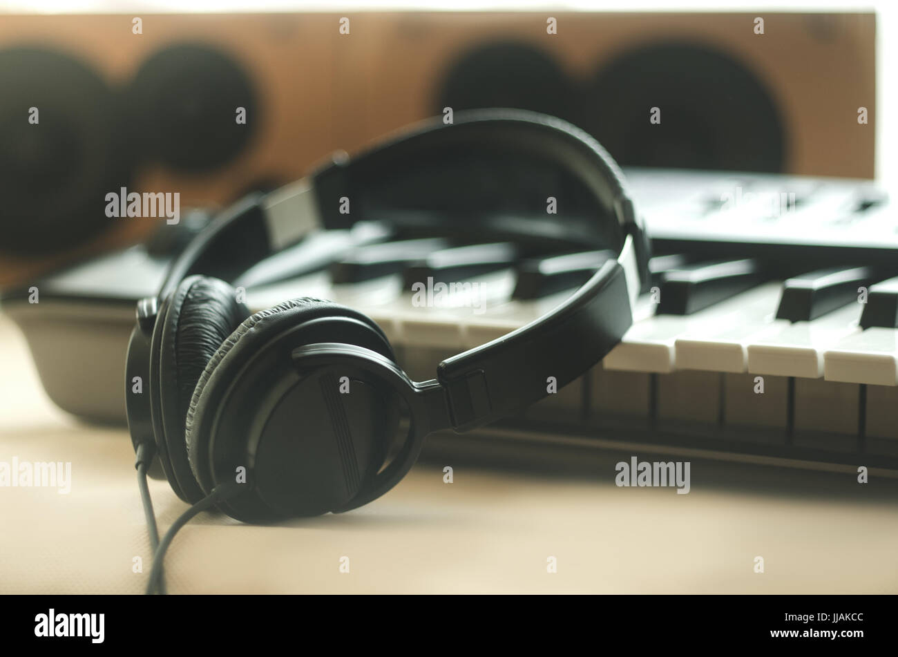 The headphones are on the synthesizer. The synthesizer stands on the background of the speakers. Light photo. Front - Stock Image