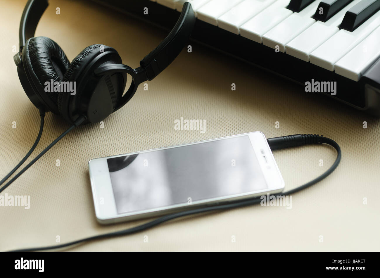 Headphones connected to the phone lying next to synthesizer on a light background. Side view - Stock Image