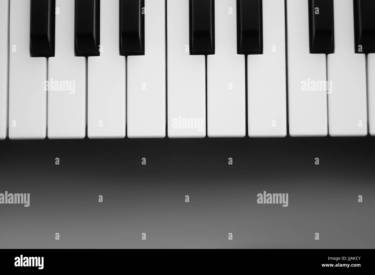 Keyboard synthesizer on a gray background. Black and white photo. View from above - Stock Image