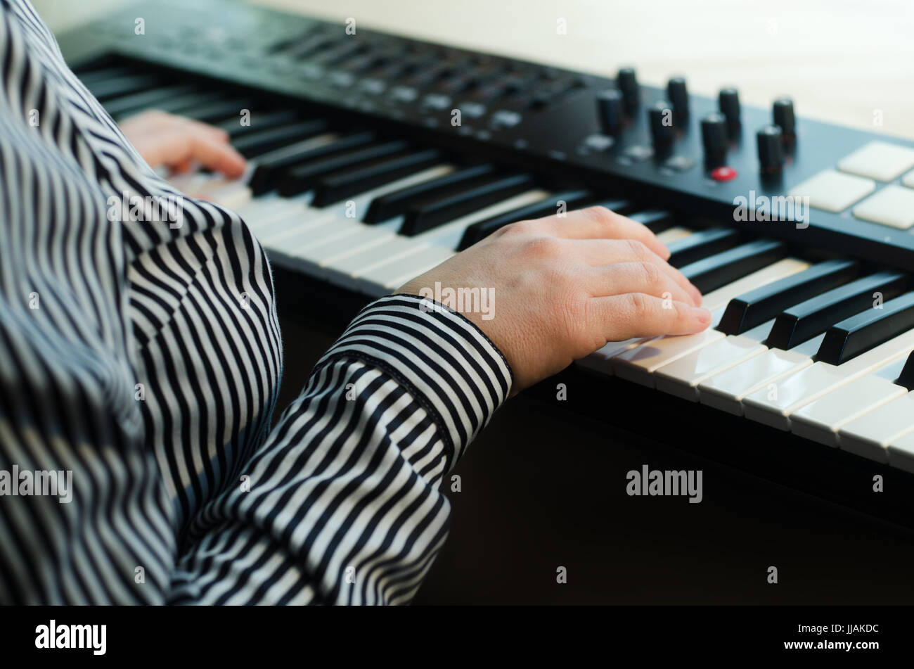 A woman in a striped shirt plays a synthesizer. In the frame the body. Side view. Light background - Stock Image