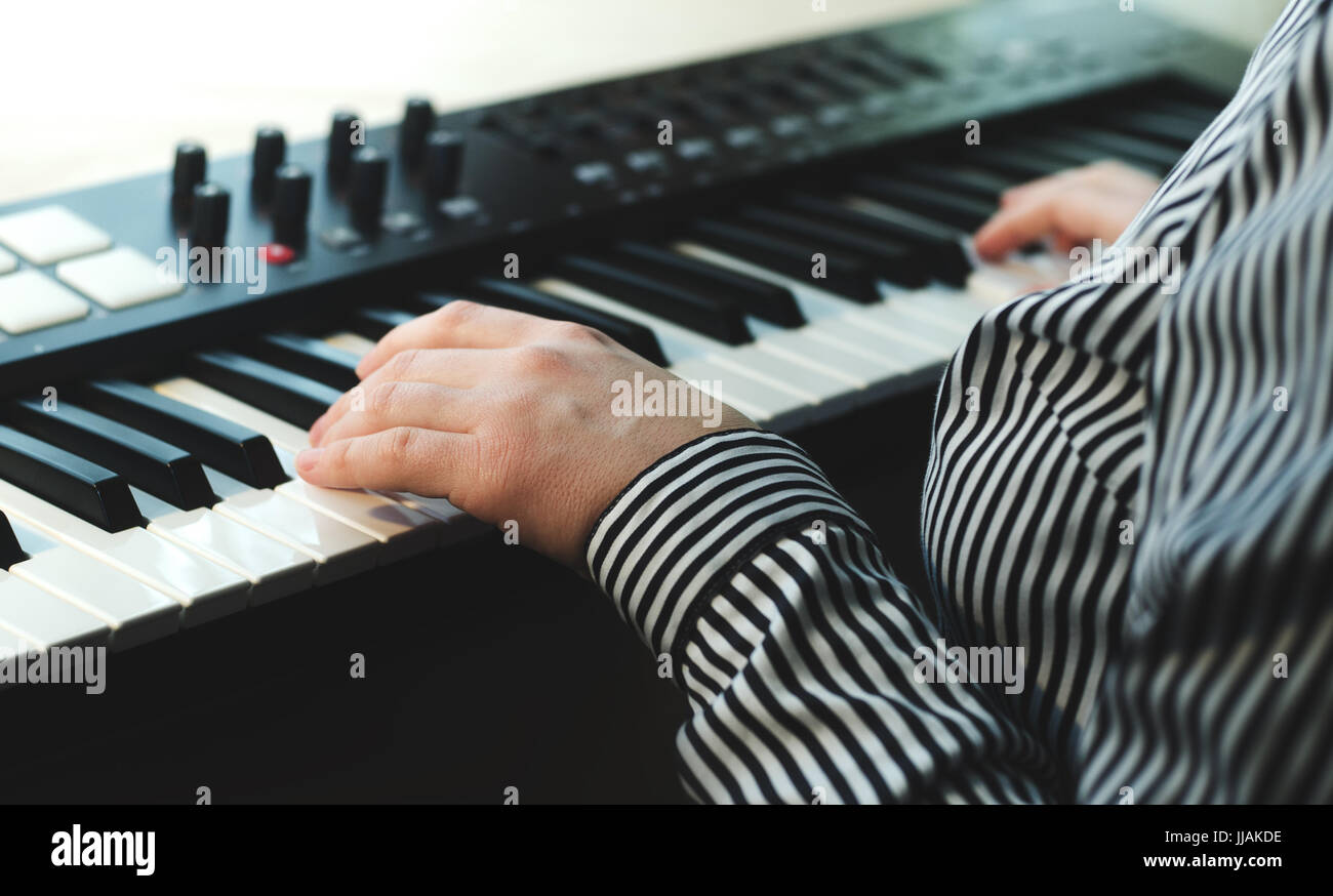 A woman in a striped shirt plays a synthesizer. There are two hands in the frame. Side view. Light background - Stock Image