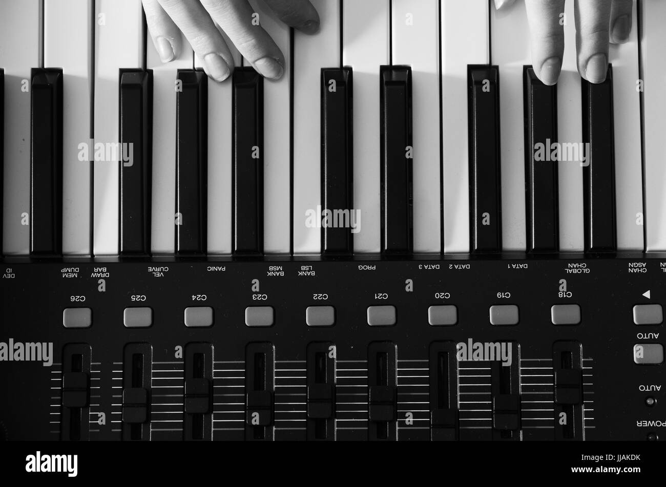 Female hands are playing a synthesizer. Black and white photo. View from above. Horizontal photo - Stock Image