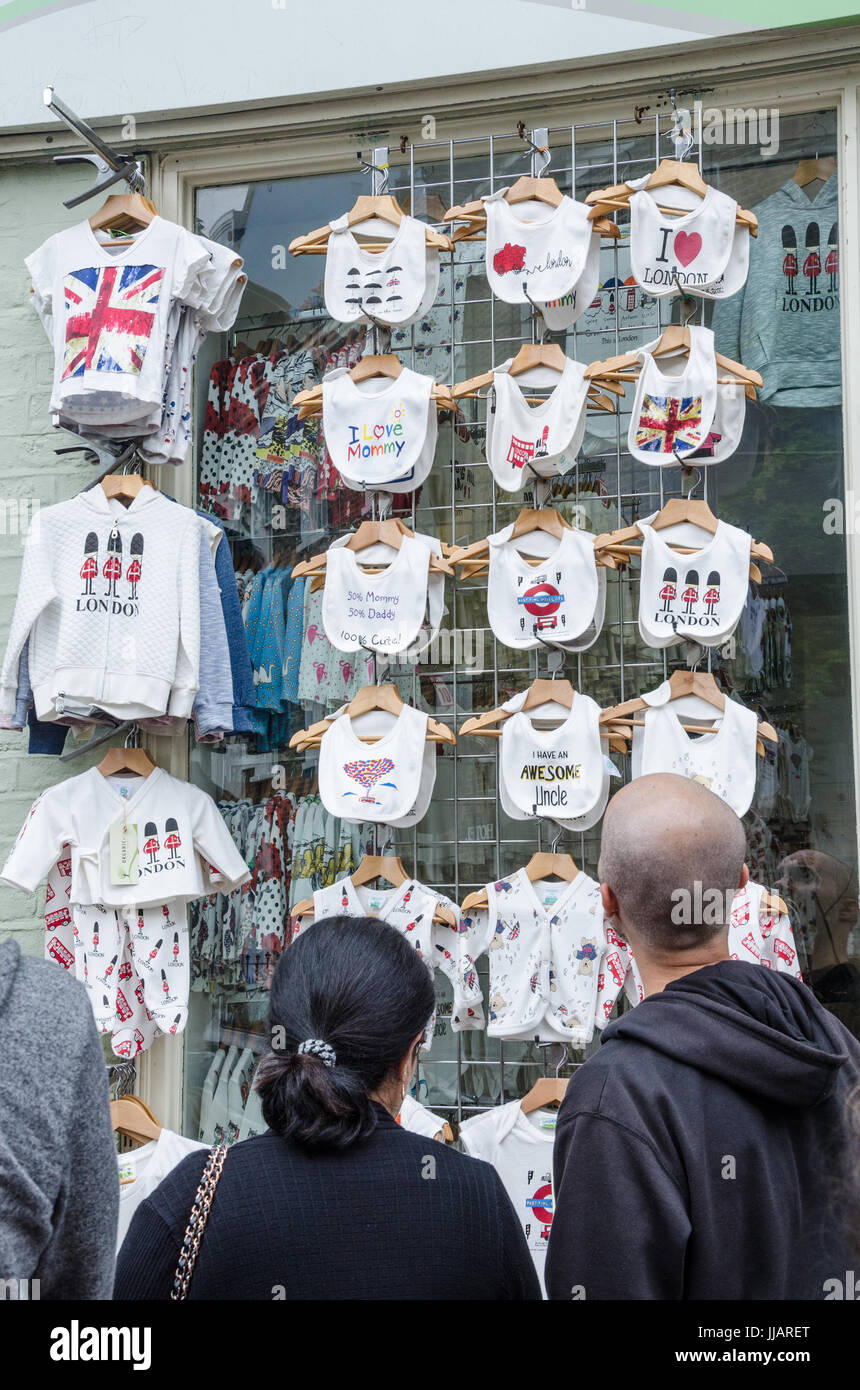 Customers brows bibs on hangers displayed outside  shop. - Stock Image