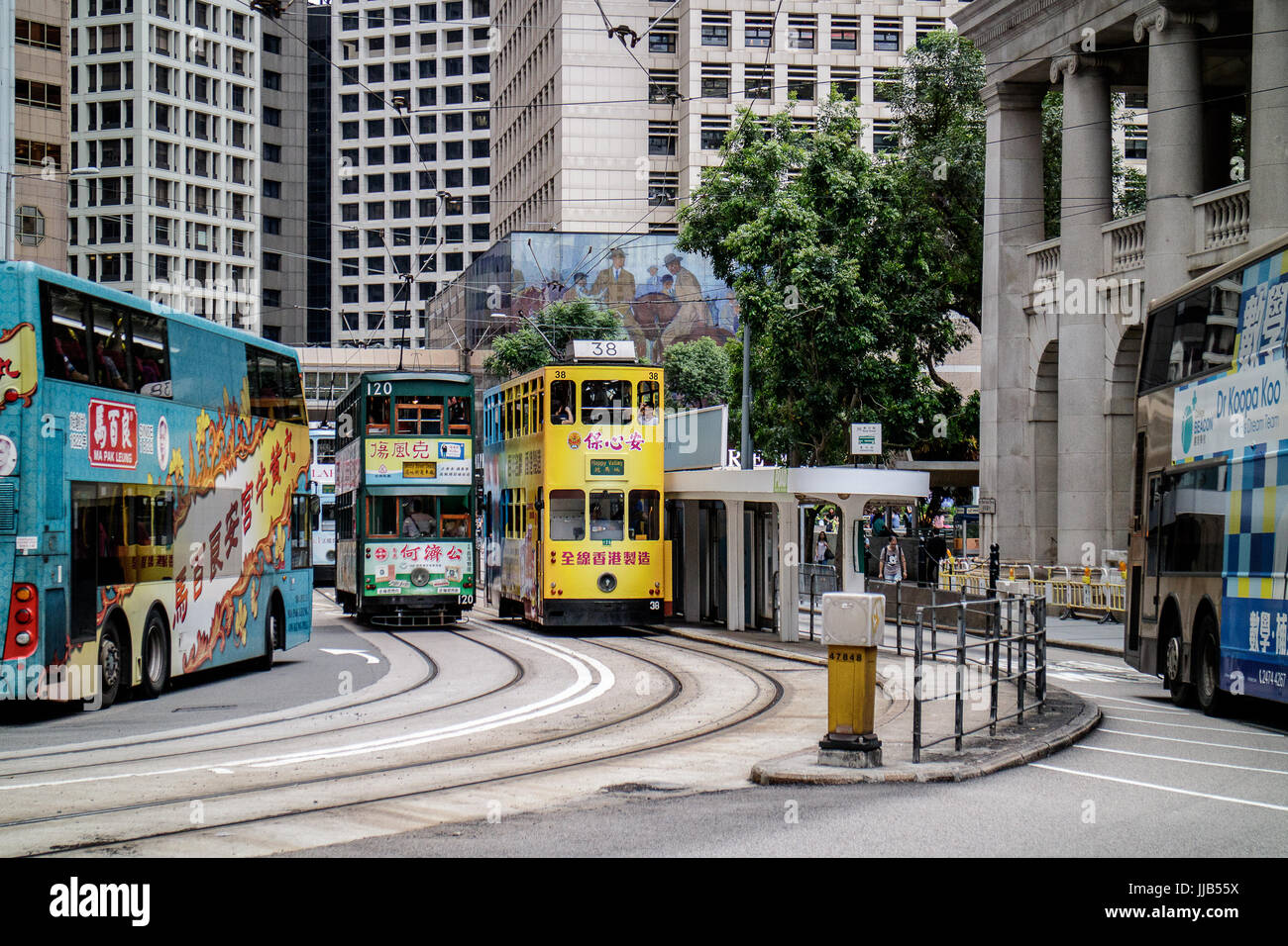 Colorful, iconic double-decker trams of Hong Kong at Bank Street stop - Stock Image